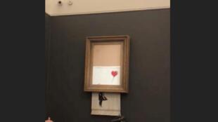 """لوحة """"فتاة مع بالون"""" للفنان البريطاني مجهول الهوية بانكسي تظهر ممزقة بعد بيعها في مزاد بلندن يوم السبت"""