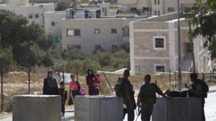 فلسطينيون يسيرون بالقرب من شرطة الحدود الاسرائيلية عند حاجز  في القدس الشرقية 15 أكتوبر 2015.