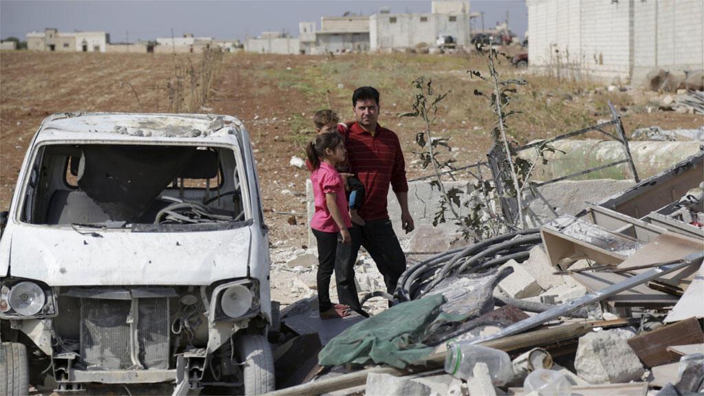 مدنيون يقفون على أنقاض موقع تضرر من قصف في ريف ادلب