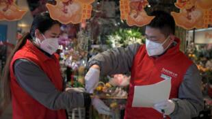 موظف في إحدى المحلات الصينية يقيس درجة حرارة زميلته قبل السماح لها بالدخول - بكين