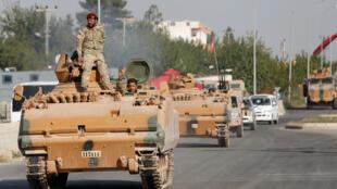 أفراد من الجيش الوطني السوري، المعروف باسم الجيش السوري الحر، يركبون سيارة مدرعة في بلدة سيلينبار الحدودية التركية-