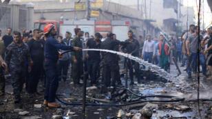 رجل إطفاء يرش الماء في موقع انفجار سيارة مفخخة أمام كنيسة في القامشلي-