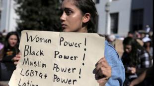 """فتاة تحمل لافتة مكتوب عليها """"قوة النساء, قوة السود, قوة المسلمين.....) في مظاهرة مناهضة لترامب في كاليفورنيا"""