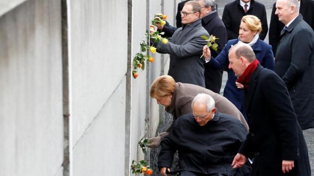 المستشارة الألمانية أنغيلا ميركل ورئيس البرلمان ومدير مؤسسة جدار برلين أكسل كلاوسنيير يضعون زهورا في ذكرى مرور 30 عاما على سقوط جدار برلين