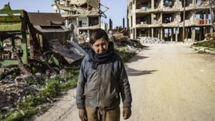 شاب يقف لالتقاط صورة وسط المباني المدمرة في بلدة كوباني الكردية السورية، المعروفة أيضًا باسم عين العرب، شمال محافظة حلب في 25 فبراير 2021.