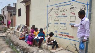 أطفال هنود وأستاذهم يتعلمون في الشارع
