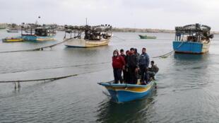 صيادون فلسطينيون على متن قارب يعودون بعد قرار إسرائيل بمنعهم من الصيد