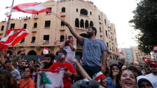 المتظاهرون يحملون الأعلام الوطنية خلال مظاهرة مناهضة للحكومة في بيروت-