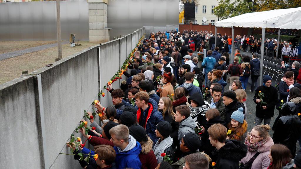 وقوف الناس أمام جدار برلين-