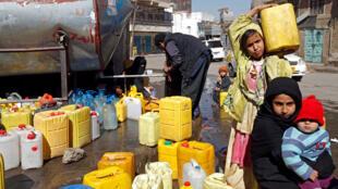 فتاة تحمل وعاء مملوء بالماء الصالح للشرب  في صنعاء