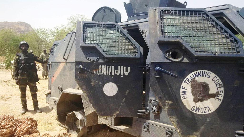 عسكري كاميروني يقف وراء سيارة مصفحة لتنظيم بوكو حرام وقع تحطيمها