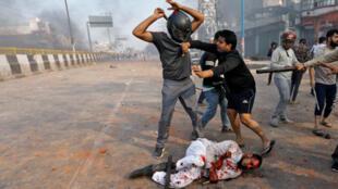 أحد الأشخاص من الذين يدعمون قانون الجنسية الجديد يضرب رجلا مسلما خلال اشتباكات مع المعارضين للقانون الجديد في نيودلهي يوم 25 فبراير/ شباط 2020