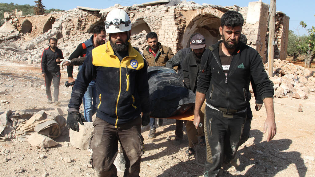 عناصر من الدفاع المدني السوري يحملون جثة شخص قُتل خلال غارة جوية  جنوب محافظة إدلب يوم 17 نوفمبر / تشرين الثاني 2019