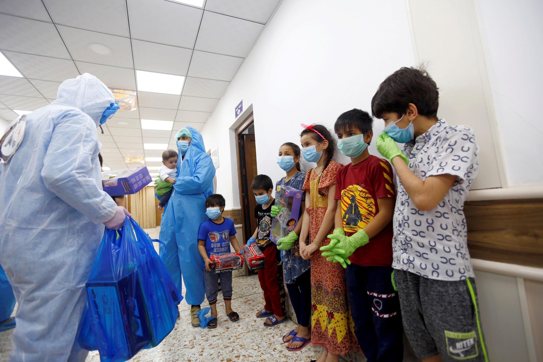 أطفال شفوا بعد إصابتهم بالكورونا، ويوزع عليهم الطاقم الطبي الهدايا احتفالا بالشفاء، النجف، العراق