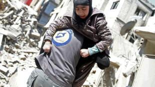 أحد عمال الإنقاذ يحمل طفلة جريحة بعد القصف