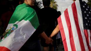 شخصان يحملان العلم الأميركي والمكسيكي ويشبكان الأيادي