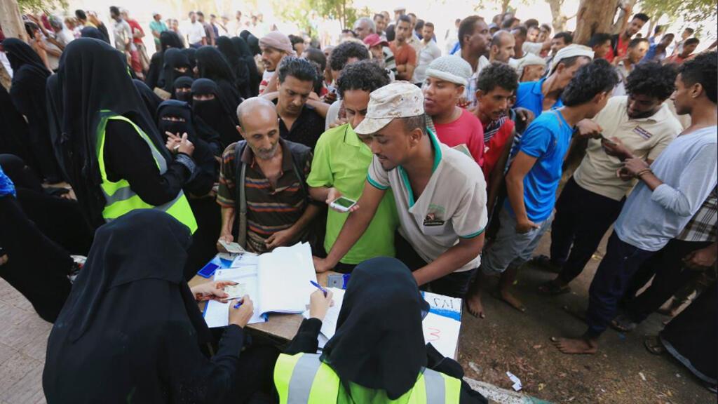 أشخاص يتجمعون عند مركز لتوزيع المساعدات تابع للأمم المتحدة في مدينة الحديدة