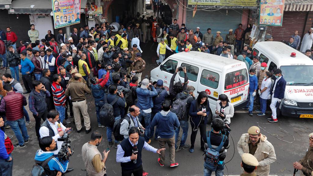 سيارة إسعاف تشق طريقها نحو موقع حريق اجتاح مصنع كان ينام فيه العمال في نيودلهي-