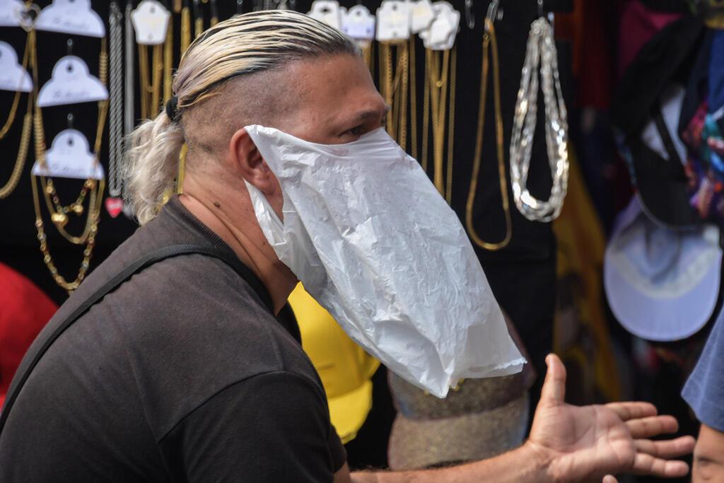 بائع متجول يرتدي حقيبة بلاستيكية كإجراء وقائي ضد انتشار الفيروس التاجي في وسط مدينة ساو باولو بالبرازيل