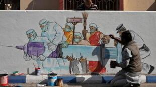 رجل يرسم صورة ترمز للقاح ضد فيروس كورونا في الهند