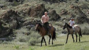 رئيس الوزراء الروسي فلاديمير بوتين يمتطي حصانا خلال إجازته خارج بلدة كيزيل في جنوب سيبيريا.