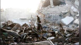رجلان وسط حطام مبنى دمرته ضربة جوية في صنعاء
