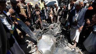 يمنيون يقفون بالقرب من محرك لطائرة من دون طيار تم اسقاطها في صنعاء في 01-10-2017