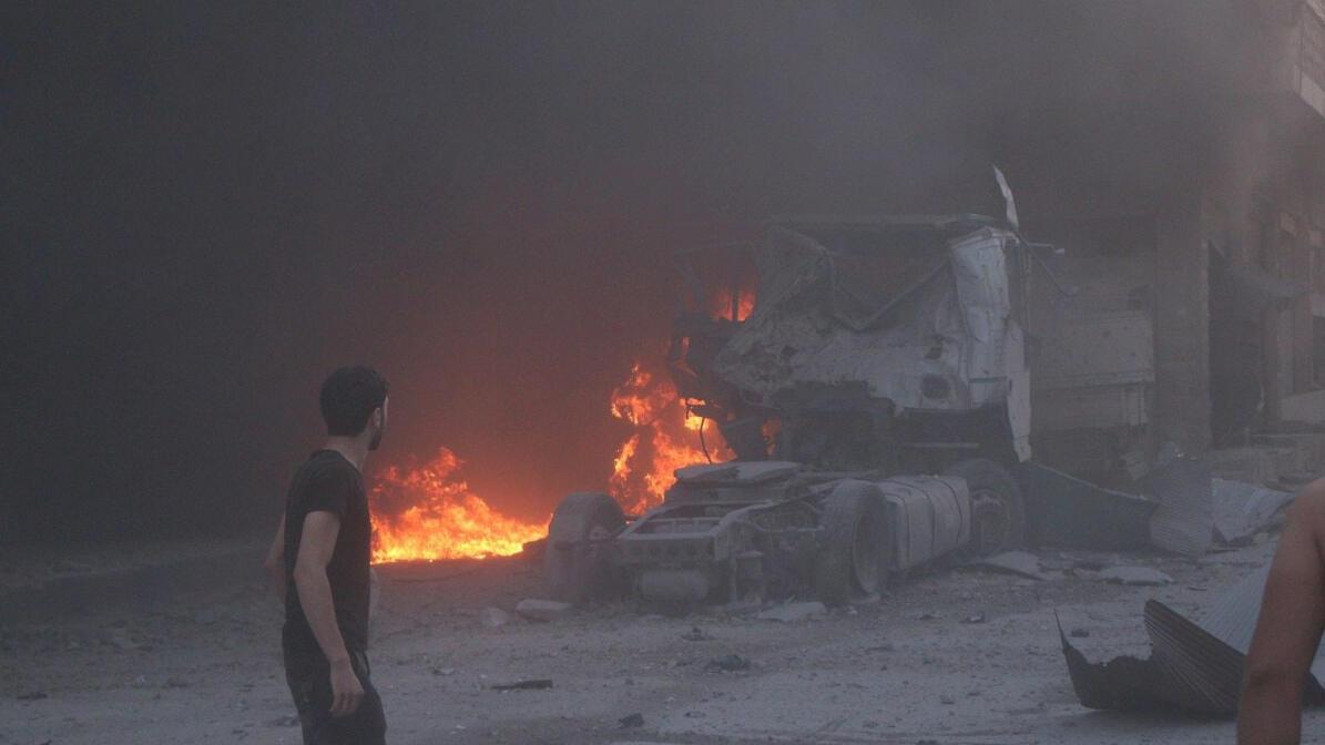 أشخاص يمشون بجوار النار والحطام وشاحنة تالفة بعد غارة جوية قاتلة ، يقال إنها في معرة النعمان ، محافظة إدلب ، سوريا 28 أغسطس ، 2019