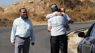 إسرائيليون قرب مكان الحادث حيث قال الجيش الإسرائيلي إنه تم العثور على جندي إسرائيلي طعن حتى الموت بالقرب من مستوطنة يهودية خارج مدينة الخليل الفلسطينية في الضفة الغربية التي تحتلها إسرائيل.