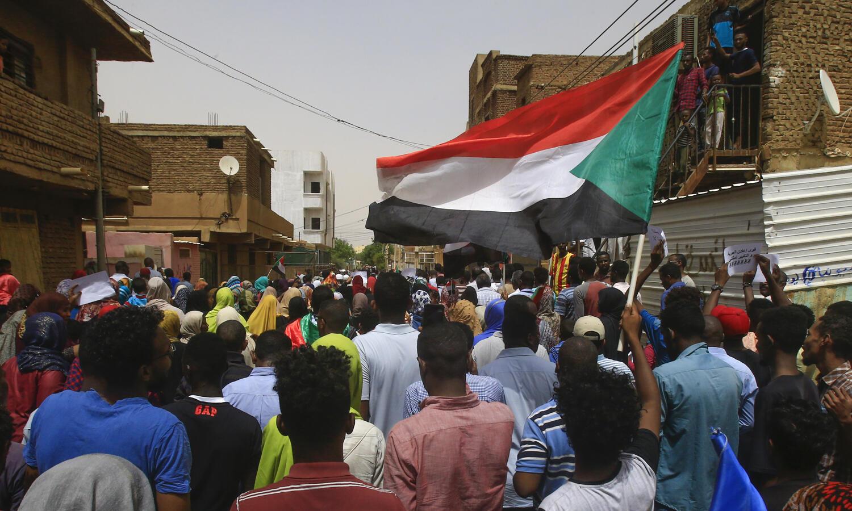 متظاهر سوداني يلوح بالعلم الوطني خلال مظاهرة حاشدة في الخرطوم