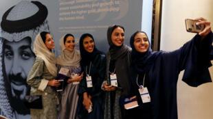 نساء سعوديات يلتقطن صورًا بجوار صورة ولي العهد السعودي الأمير محمد بن سلمان