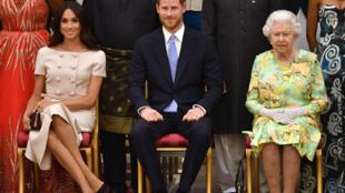 ملكة بريطانيا إليزابيث الثانية والأمير البريطاني هاري وميغن  ماركل أثناء حفل توزيع جوائز كوينز للقادة الشباب في قصر باكنغهام في لندن يوم  26 يونيو 2018