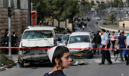 صبي إسرائيلي أمام موقع الهجوم بالسيارة الذي قام به فلسطيني في القدس (الصورة من رويترز)