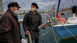 الأرجنتيني خوان مانويل باليستيرو (على اليمين) يتحدث مع والده كارلوس عند وصوله إلى ميناء مار ديل بلاتا في البرتغال ، يوم 20 يونيو 2020 بعد ابحار دام 85 يومًا بسبب وباء كورونا