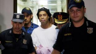 النجم السابق لكرة القدم البرازيلية رونالدينيو مكبل اليدين في طريقه إلى المحكمة العليا في باراغواي يوم 7 مار/آذار 2020