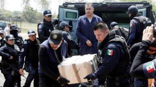يحمل أفراد الشرطة الفيدرالية صندوقاً يحتوي على عبوات من الكوكايين