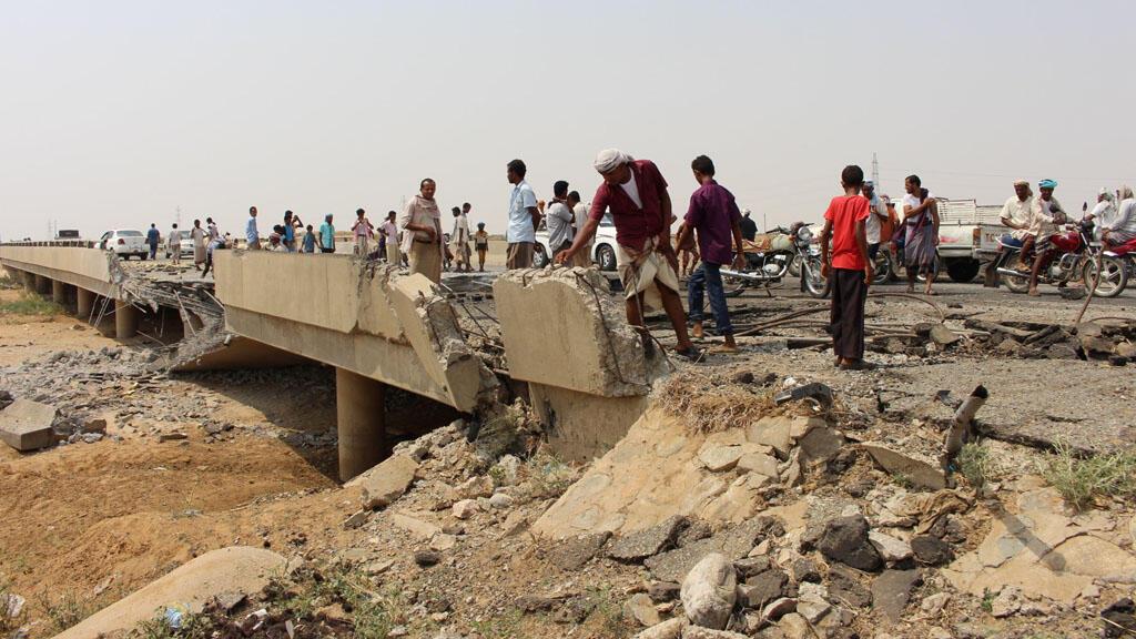 يمنيون يتفحصون الأضرار التي لحقت بجسر ضربته غارة جوية للتحالف بقيادة السعودية بالقرب من مدينة حراد شمال غرب اليمن 23-09-2017