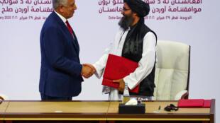 مصافحة بين رئيس الوفد المفاوض من قبل طالبان (يمين) ورئيس الوفد المفاوض من قبل واشنطن بعد توقيع الاتفاق
