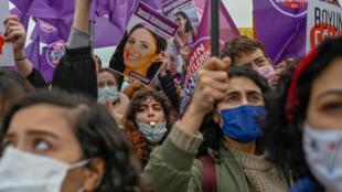 """متظاهرات في اسطنبول يوم 20 مارس 2021 يرفعن لافتات وصورة لامرأة قتلها رجال كتب عليها """"لن نسكت"""" خلال مظاهرة ضد انسحاب تركيا من اتفاقية اسطنبول، وهي اتفاقية دولية تهدف إلى حماية النساء  في العالم."""