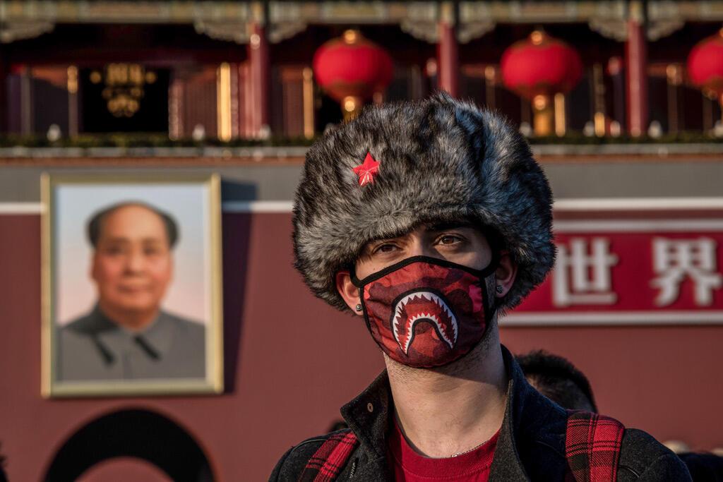سائح بريطاني يرتدي قناعاً ويلتقط صورة أمام لوحة كبيرة للزعيم الشيوعي ماو تسي تونغ عند بوابة تيانانمن في بكين