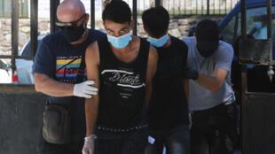 لاجئون أفغان تم أعتقاهم من قبل الشرطة اليونانية بعد الحريق الذي دمر مخيم للمهاجرين في جزيرة ليسبوس اليونانية