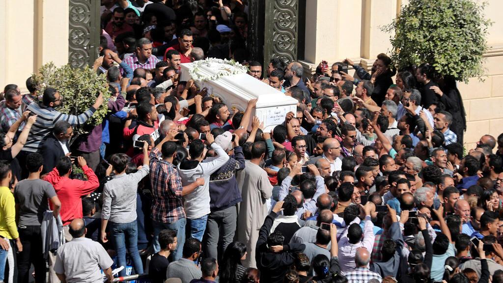 مشيعون يحملون نعشًا خلال جنازة المسيحيين الأقباط الذين قتلوا في هجوم ، في المنيا ،