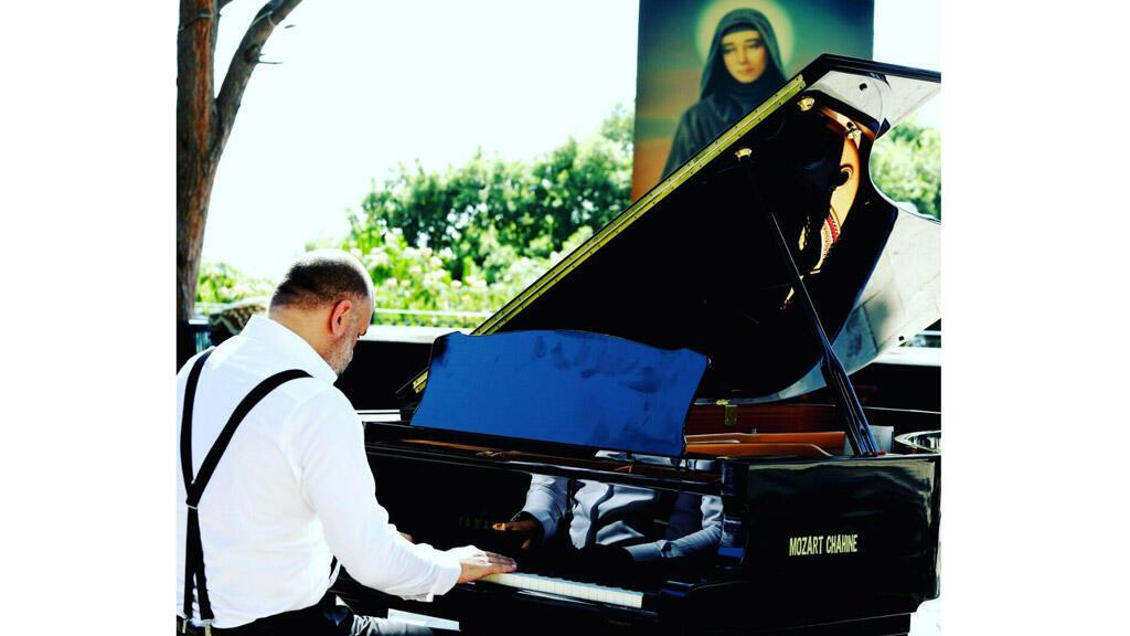 """الموسيقي اللبناني جان كيروز وأمامه صورة للقديسة """"رفقة"""""""