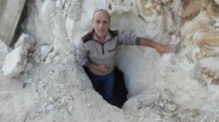 طاهر أبو حمدان على مدخل المغارة المكتشفة في بلدة كوكبا