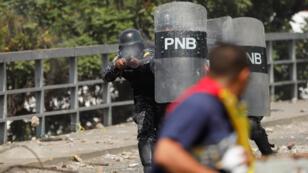 شرطي يطلق الرصاص المطاط على أحد المتظاهرين ضد سلطة نيكولاس مادورو