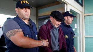 يرافق ماريو ساندوفال ضباط الشرطة بعد ترحيله من فرنسا -