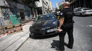 ضابط شرطة  في أحد الشوارع بجانب سيارة  متضررة من زلزال في أثينا