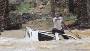 يمني يحاول انقاذ سيارة جرفتها مياه الفيضانات في جزيرة سقطرى اليمنية 2 نوفمبر 2015.