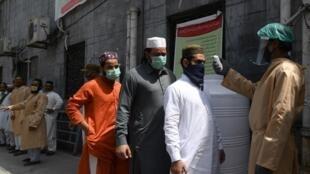 مصلون أمام مسجد  ينتظرون دورهم  لقياس حرارتهم بسبب تفشي فيروس كورونا