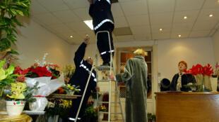 فريق من رجال الإسعاف يتفحصون جهاز التكييف في محل لبيع الزهور، في منطقة دروكور الفرنسية